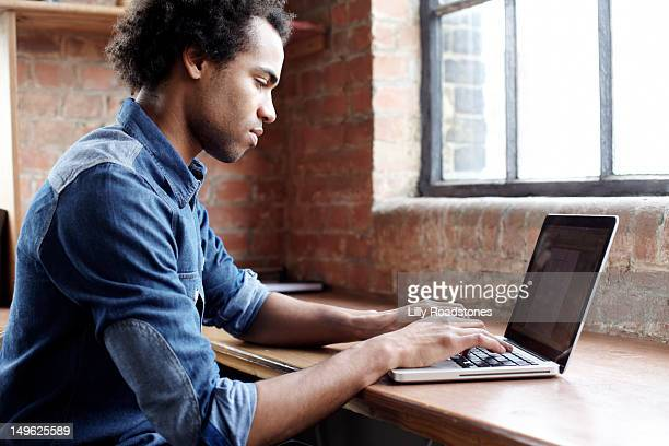 young guy using laptop at desk - typing stock pictures, royalty-free photos & images
