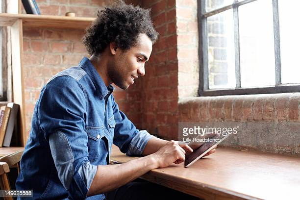 young guy using tablet computer at desk - newtechnology stock pictures, royalty-free photos & images