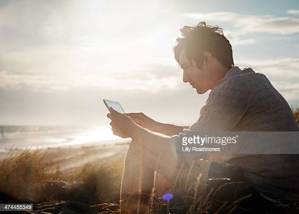 young guy using tablet computer in sand dunes - portability stock pictures, royalty-free photos & images