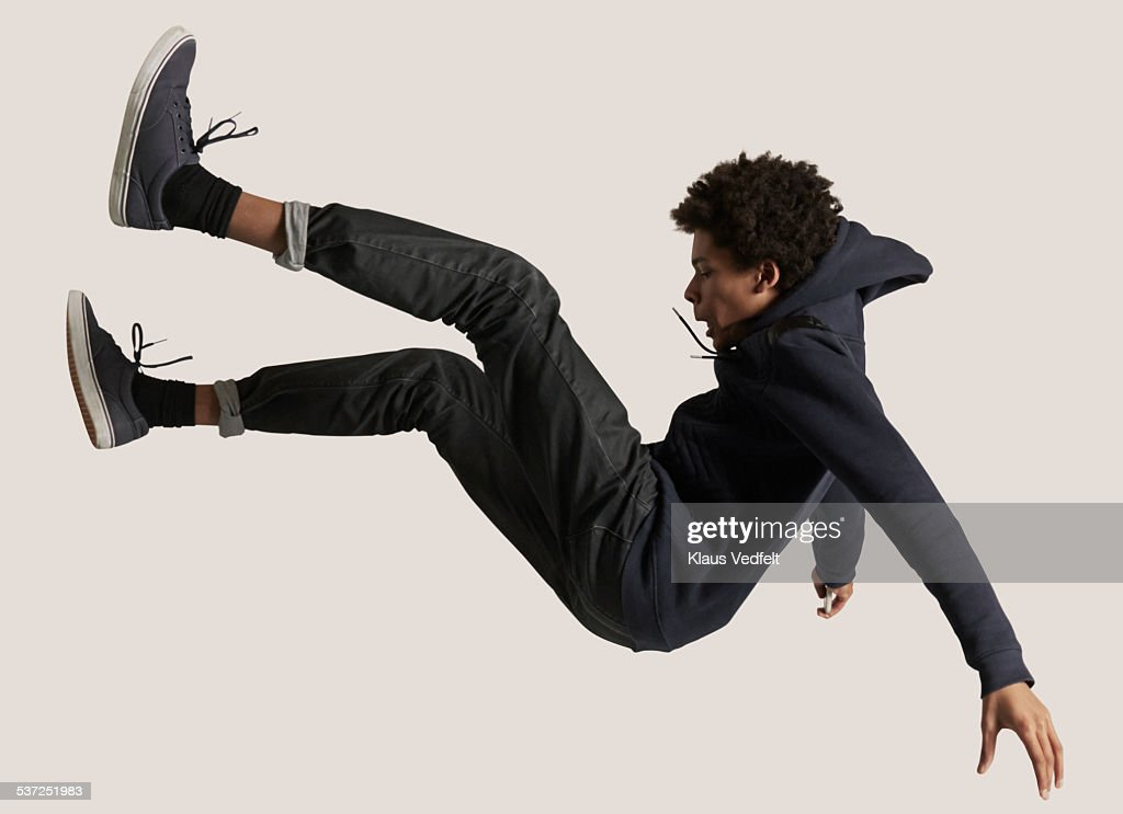 Young guy wearing hoodie, falling in the air : Stock Photo