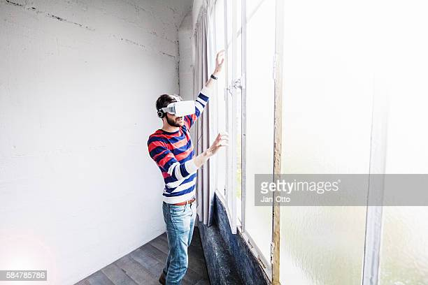 Young guy wearing virtual reality goggles and headphones at window