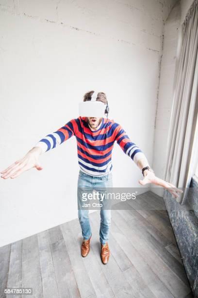 Chico joven usando gafas de realidad virtual y los auriculares