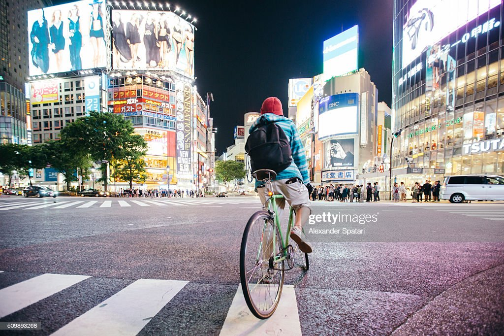 Young guy with backpack riding a bike on Shibuya crossing in Tokyo, Japan : Stock Photo
