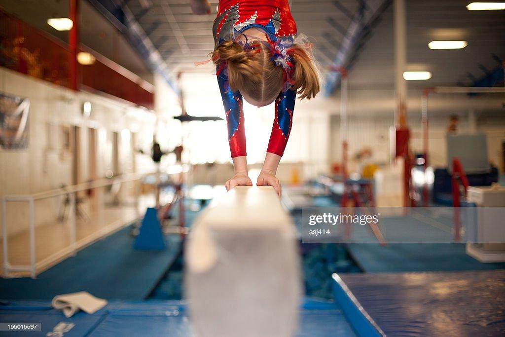 Young Gymnast Doing Handstand on Balance Beam : Stock Photo