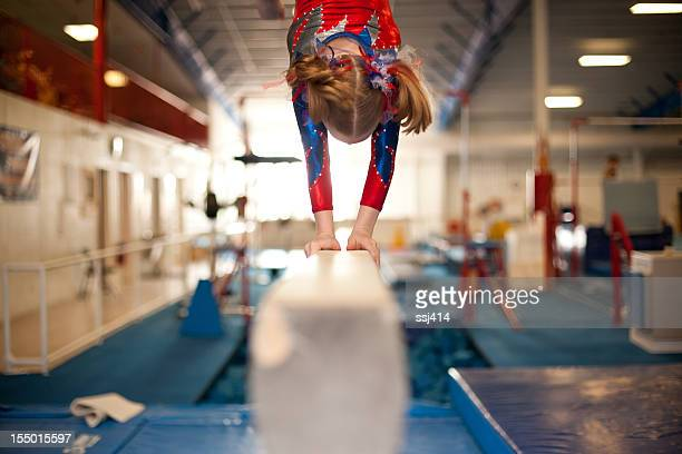 young gymnast doing handstand on balance beam - gymnastics stock pictures, royalty-free photos & images