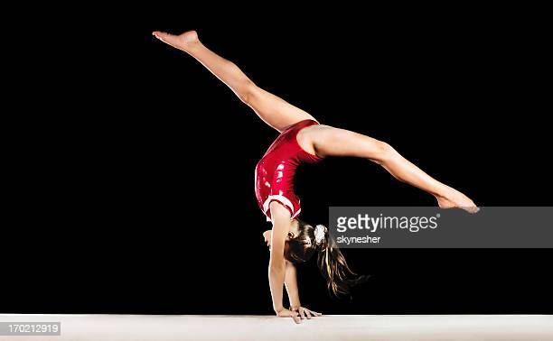 Young gymnast girl exercising on balance beam.