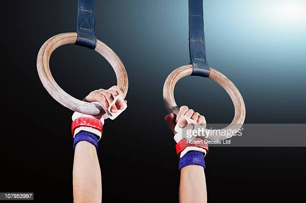 young gymnast hanging from rings - gymnastics stock pictures, royalty-free photos & images