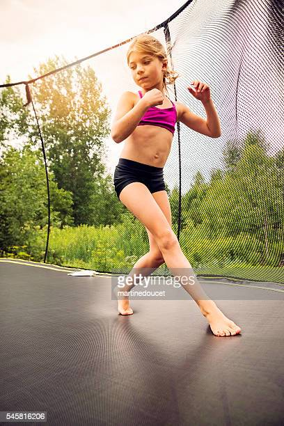 Young gymnast on a backyard trampoline in summer.
