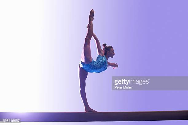 young gymnast performing on balance beam - gymnastics stock pictures, royalty-free photos & images