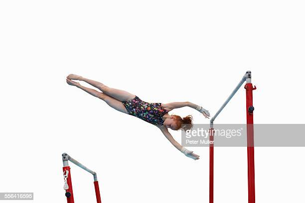 young gymnast performing on uneven bars - horizontal bars stock pictures, royalty-free photos & images