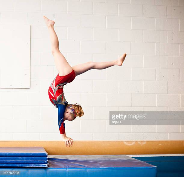 young gymnast performing walkover on balance beam - gymnastics stock pictures, royalty-free photos & images