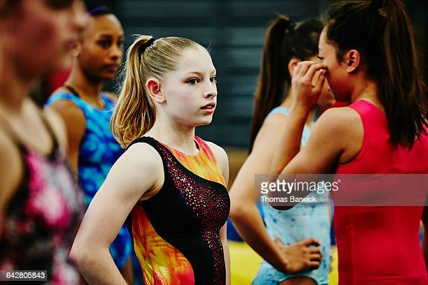 Young gymnast resting after warm-up with teammates