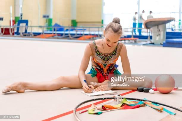 jeune gymnaste assis sur le sol, prendre des notes de ses exercices - gymnastique au sol photos et images de collection