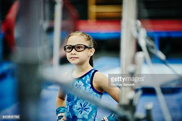 young gymnast watching teammate train on bars - gymnastics poses stock pictures, royalty-free photos & images
