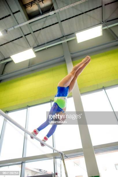 Young Gymnastics Athlete Exercising on Horizontal Bar