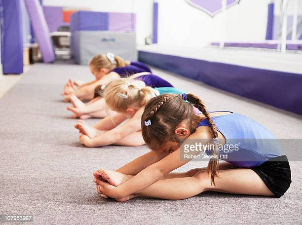 young gymnasts performing warming up routine - gymnastics stock pictures, royalty-free photos & images