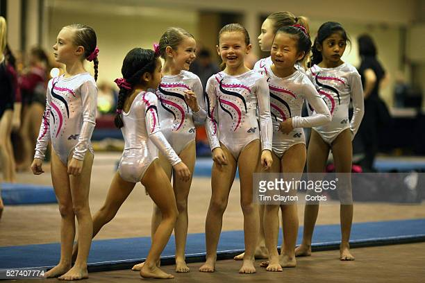 Young gymnasts share a joke during vault warm up before competition during the 21st American Invitational 2014 competition at the XL Centre Hartford...