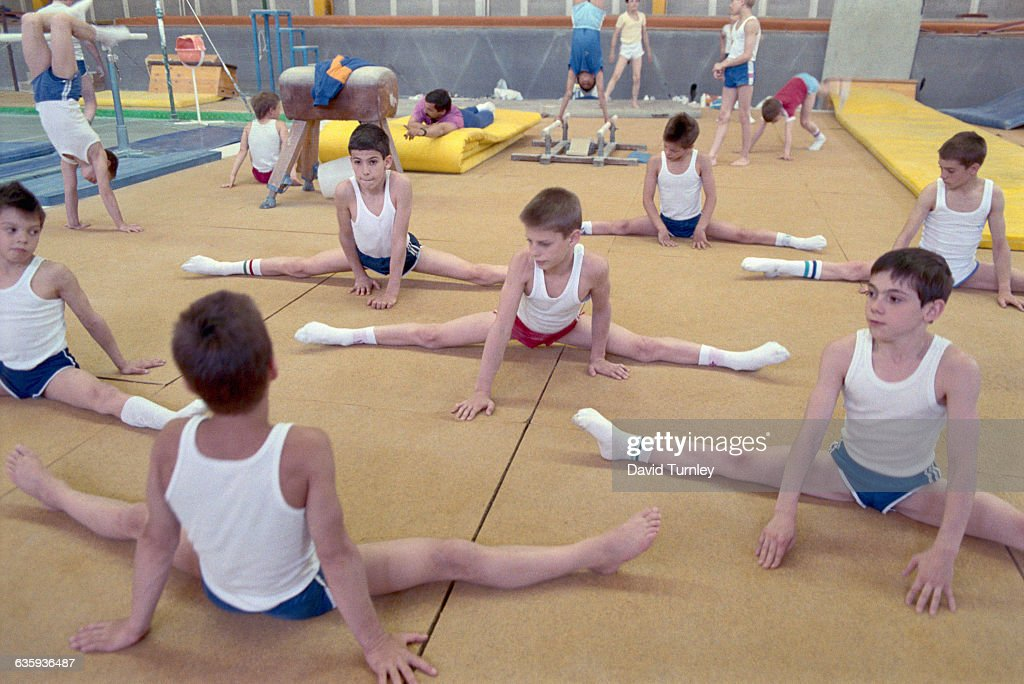 Young gymnasts stretch before practicing at a Hungarian state-controlled central sports school. The school trains students who were selected because they showed special athletic promise.