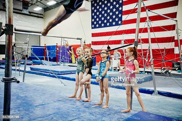 Young gymnasts watching teammate practice on bars