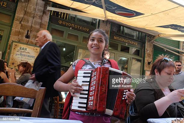 A young gypsy girl plays accordion in front of a restaurant at lunch time in Monastiraki old town on April 15 2016 in Athens Greece