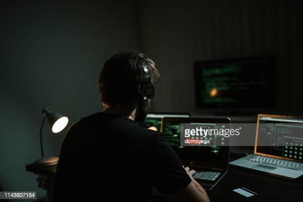 joven hacker usando computadoras portátiles en una habitación oscura - deep web fotografías e imágenes de stock