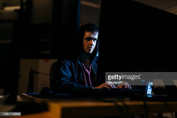 young hacker working on computer while sitting at office - focus on background stock pictures, royalty-free photos & images