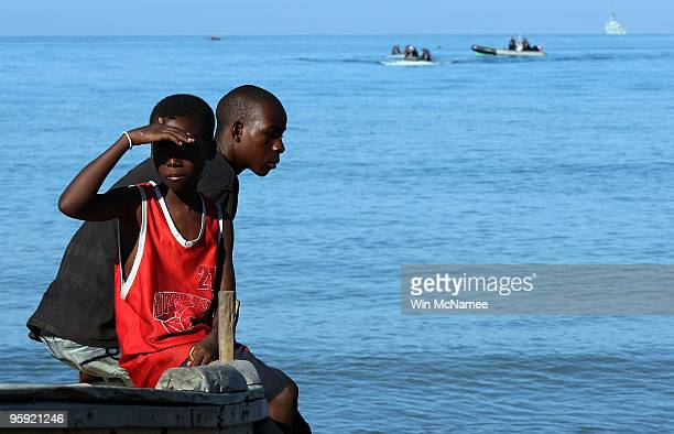 Young Haitian boys watch from the beach as crew members of the Canadian Navy vessel HMCS Athabaskan make their way to shore in the city of Leogane on...