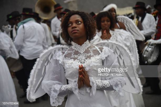 TOPSHOT A young Haitian woman dressed in an angel costume participates in a Christmas Parade on the streets of the commune of Petion Ville in the...