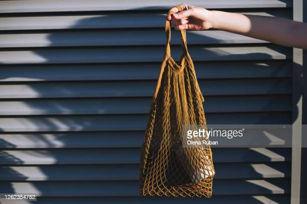 young hand holding a brown string bag with a book and cup - bag stock pictures, royalty-free photos & images