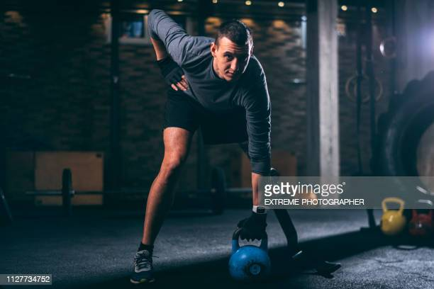 young handicapped athlete with a prosthetic leg doing a one arm kettlebell swing exercise in a gym gym - human limb stock pictures, royalty-free photos & images