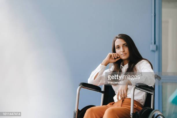 young handicapped woman sitting in wheelchair, looking worried - wheelchair stock pictures, royalty-free photos & images