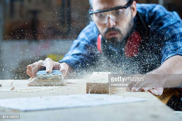 young handosme carpenter blowing off sawdust - arbeider stockfoto's en -beelden