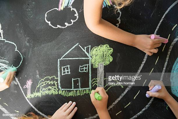 Young hands drawing home scene on chalk board