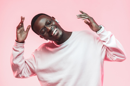 Young handsome african american man dancing, singing his favorite song with closed eyes, isolated on pink background 1090819316