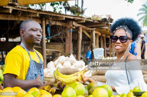 a young handsome african man feeling excited as he sells to his beautiful customer - nigeria stock pictures, royalty-free photos & images