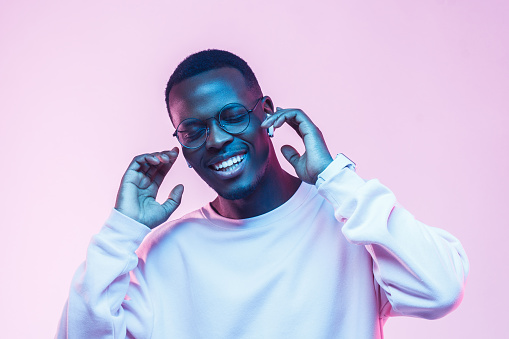 Young handsome african man in wireless headphones and listening to his favourite song, dancing, smiling with closed eyes 1093991948