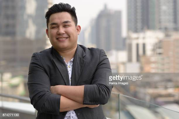 Young handsome Asian businessman enjoying life in the city of Bangkok, Thailand