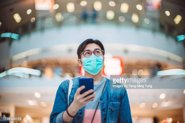 young handsome asian man in medical face mask using smartphone joyfully in shopping mall - パンデミック ストックフォトと画像