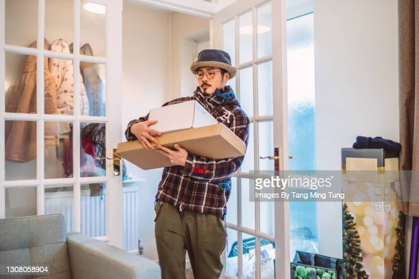 young handsome asian man receiving home delivered parcels in new house - new stock pictures, royalty-free photos & images