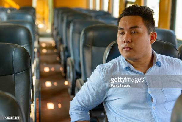 young handsome asian tourist man riding the train at the railway station - train interior stock photos and pictures