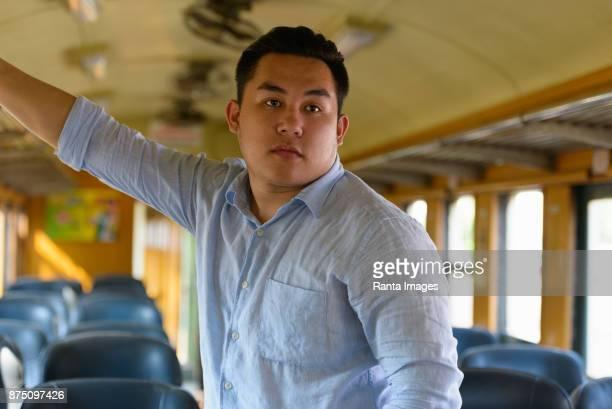 駅で電車に乗る若いハンサムなアジア観光客男