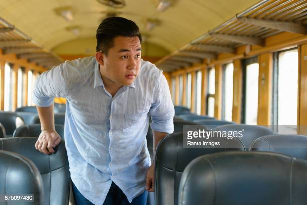 Young handsome Asian tourist man riding the train at the railway station