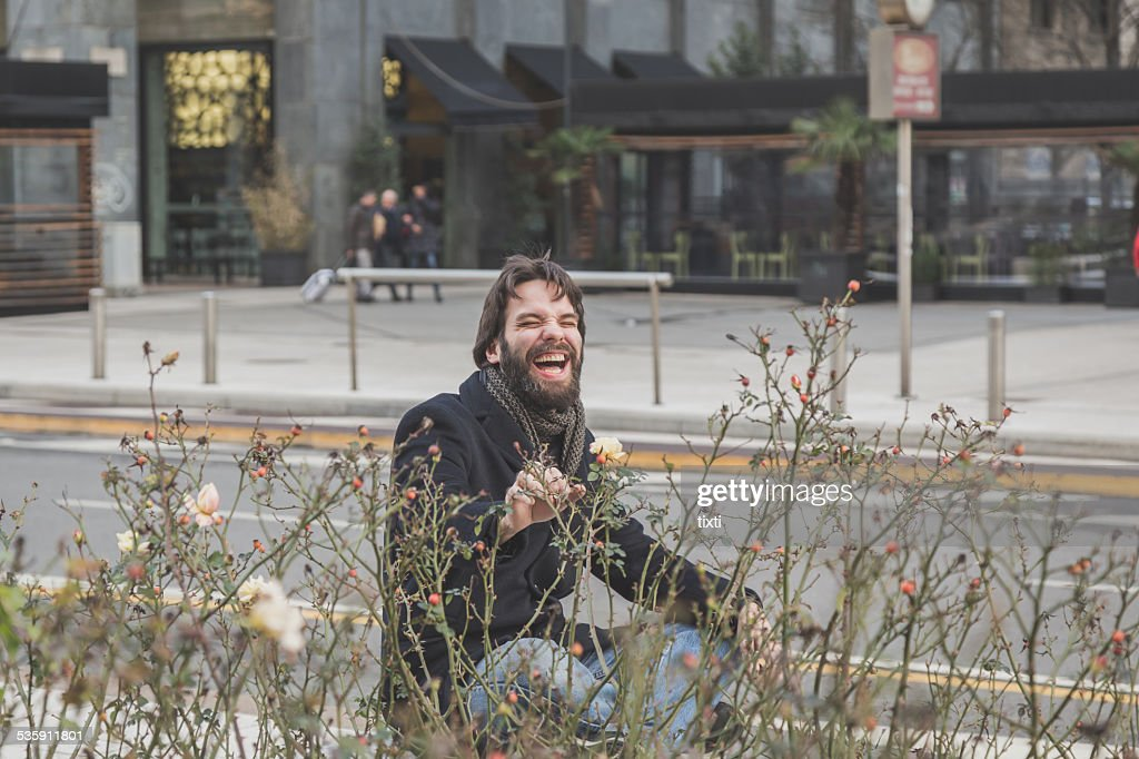 Young handsome bearded man posing in the city streets : Stock Photo