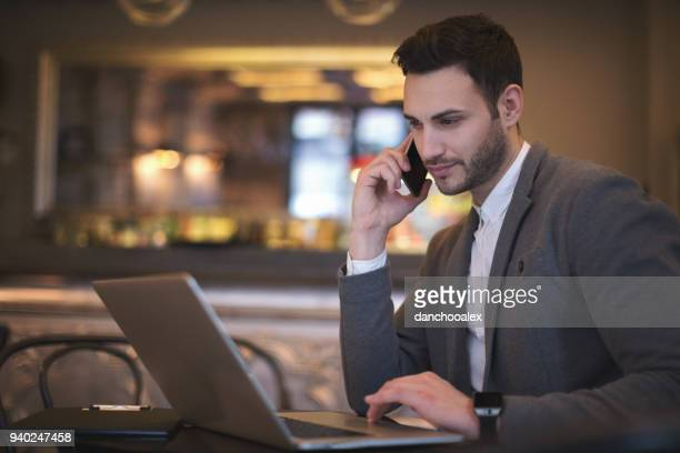 Young handsome businessman at coffee bar working