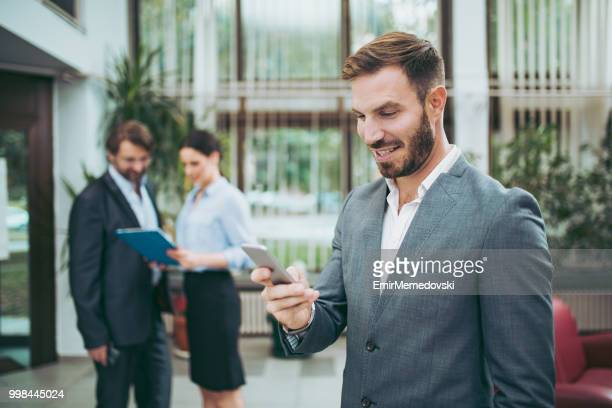 Young handsome businessman holding mobile phone and text messaging