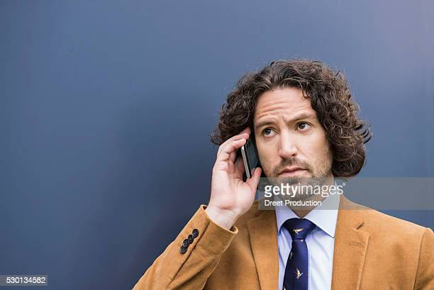 young handsome businessman long hair cell phone - brown blazer stock pictures, royalty-free photos & images
