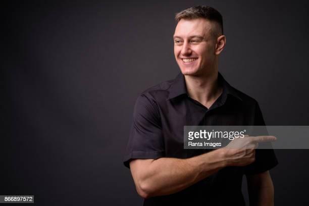 junge hübsche geschäftsmann tragen schwarzes hemd vor grauem hintergrund - menschlicher rücken stock-fotos und bilder