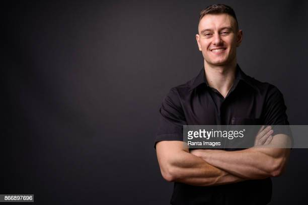 young handsome businessman wearing black shirt against gray background - half shaved hairstyle stock pictures, royalty-free photos & images