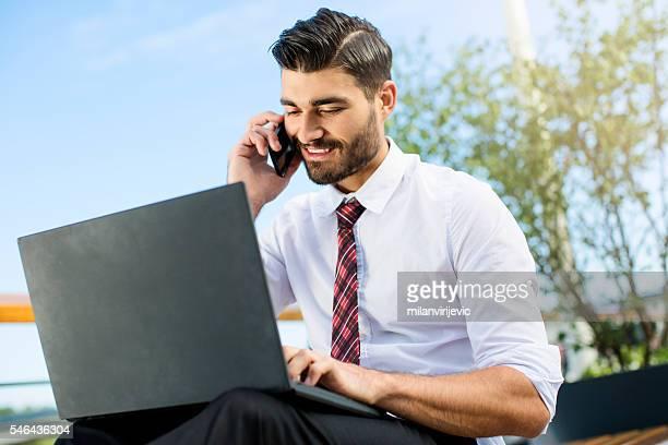 young handsome businessman working outdoors - bring your own device stock-fotos und bilder