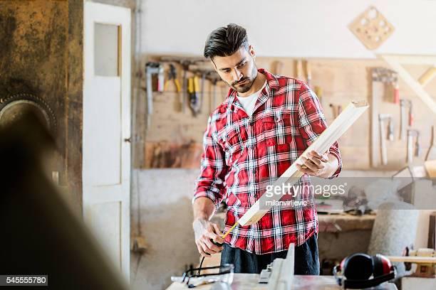 Young handsome carpenter measuring board in craft workshop
